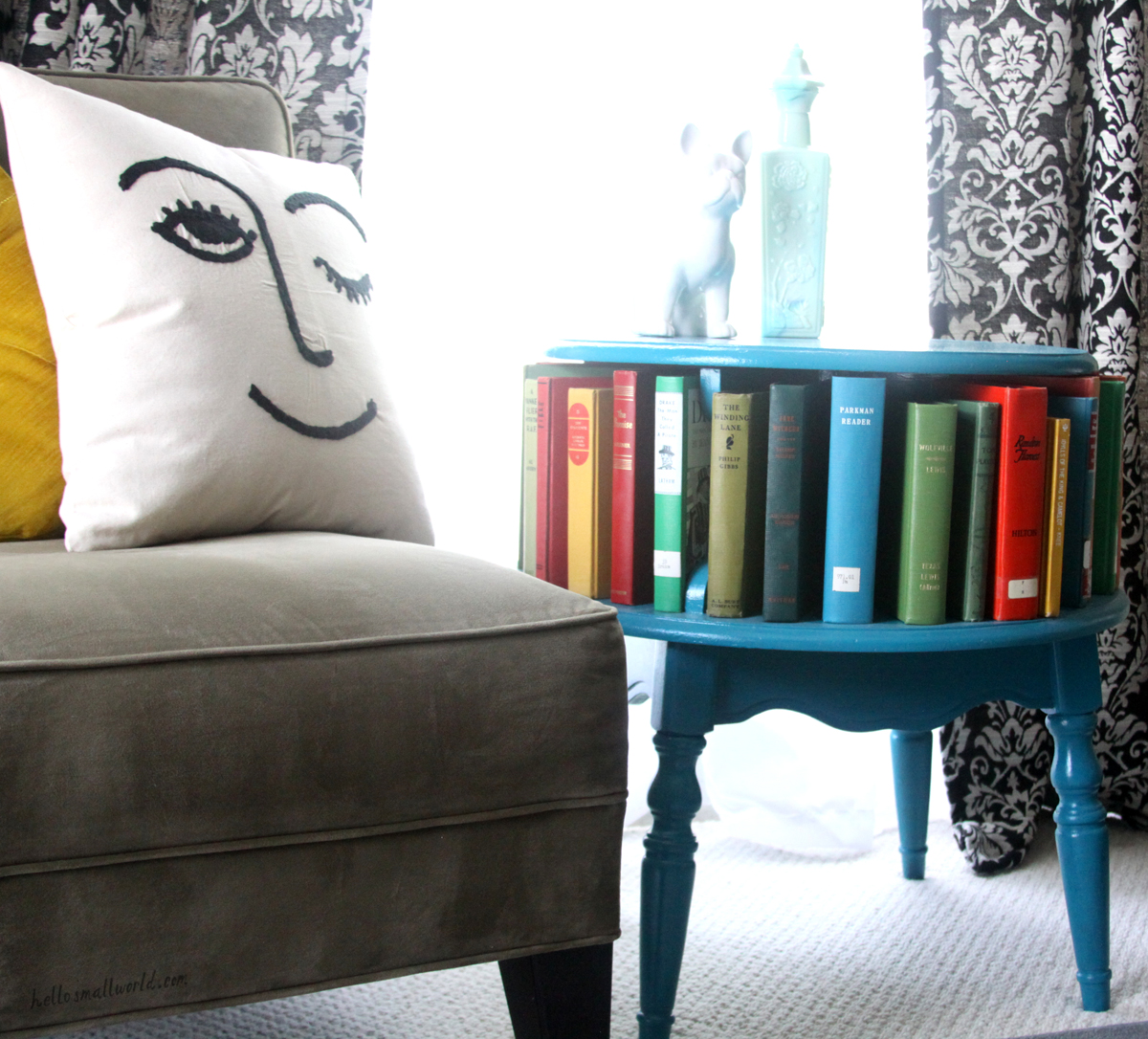 painted thrift store table with colorful vintage books in a reading nook with a winky face pillow from urban outfitters